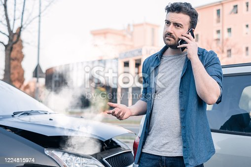 1047083324 istock photo Man calling roadside emergency after car accident 1224815974