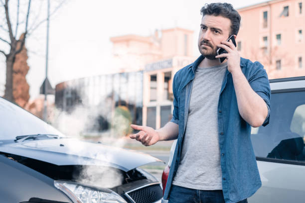 Man calling roadside emergency after car accident stock photo