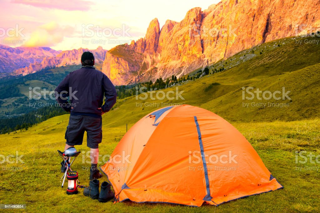 Man camping at sunset in Dolomites Alps stock photo