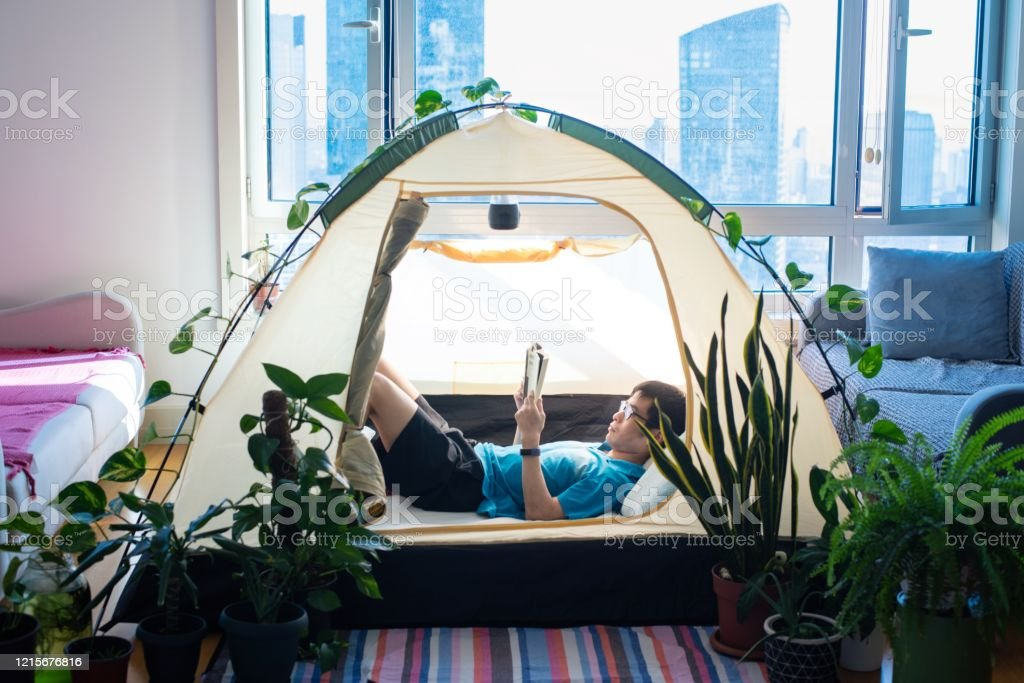 Man camping in his living room - Royalty-free 2020 Stock Photo