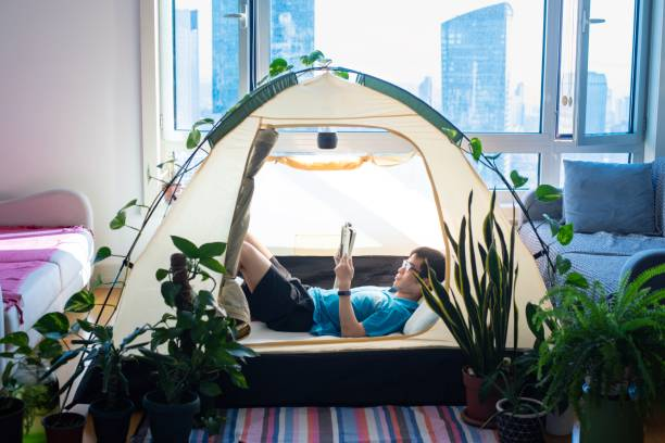 Man camping in his living room stock photo