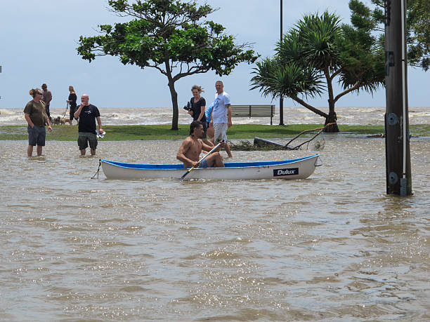 Man canoeing down Flooded Street stock photo