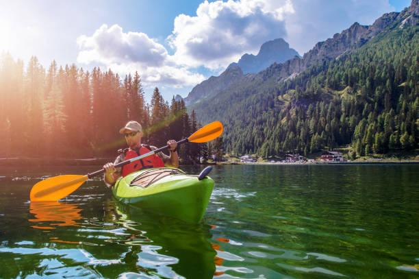 Man Canoeing In Misurina Lake In Italy stock photo