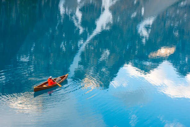 A man canoeing in Moraine Lake Lake Louise, Canada - June 22, 2015. A man canoeing in Moraine Lake in Banff National Park, Alberta, Canada. moraine lake stock pictures, royalty-free photos & images
