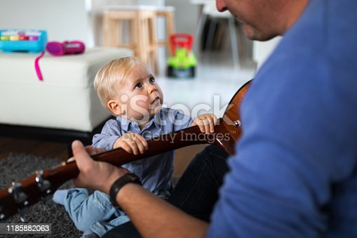 649431568 istock photo Man can`t play guitar because his son 1185882063