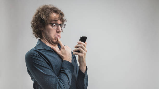 man can't use a mobile phone fearful or doubtful man looking to a smartphone with a very shocked expression because he can't understand what to do or what he watches - concept of new technology misunderstanding ignorance stock pictures, royalty-free photos & images