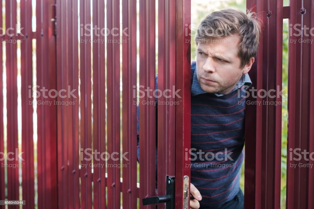 man carefully watches and looks from behind the fence, opening door stock photo