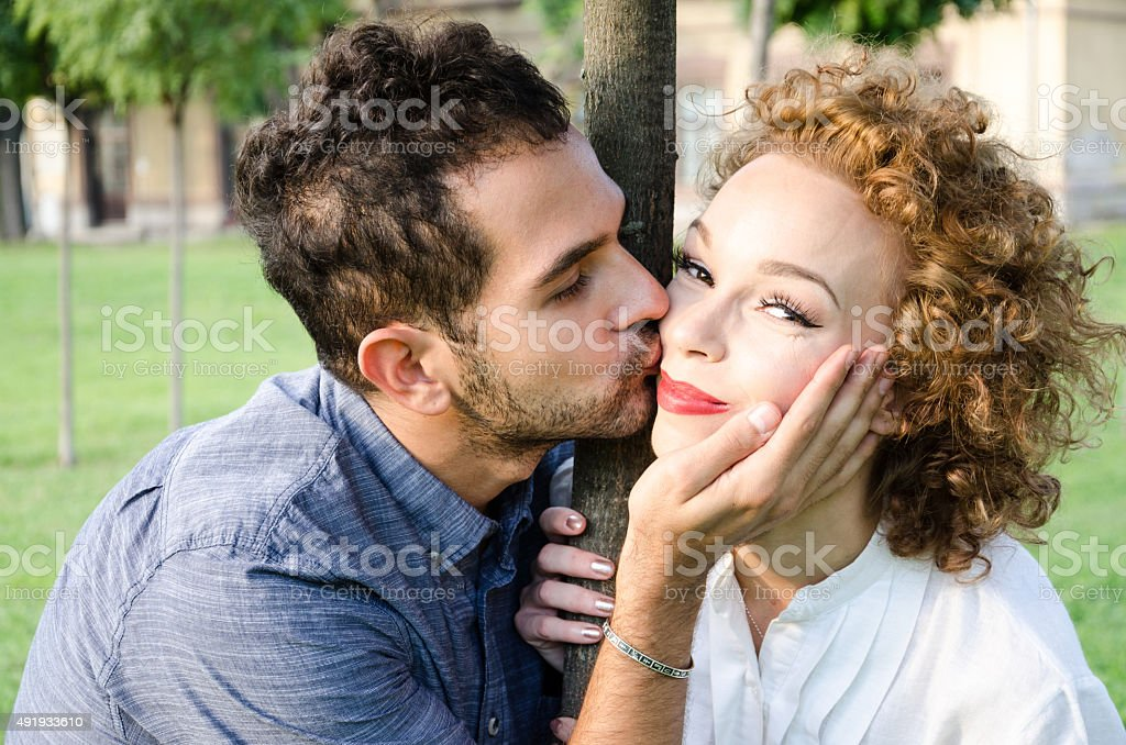 man caressing a woman in the face stock photo