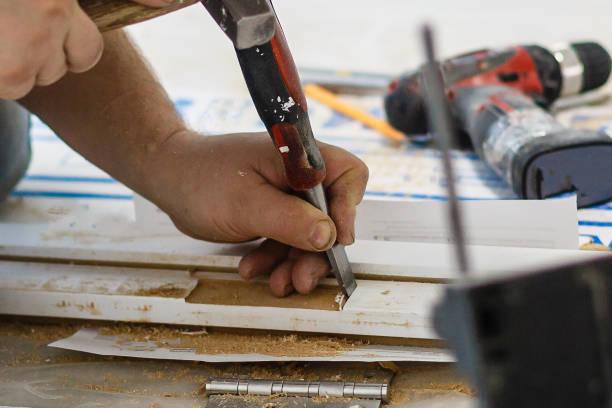 mann zimmermann macht ein loch in das holz eine tür für das schloss mit hammer und meißel hautnah - waldhandwerk stock-fotos und bilder