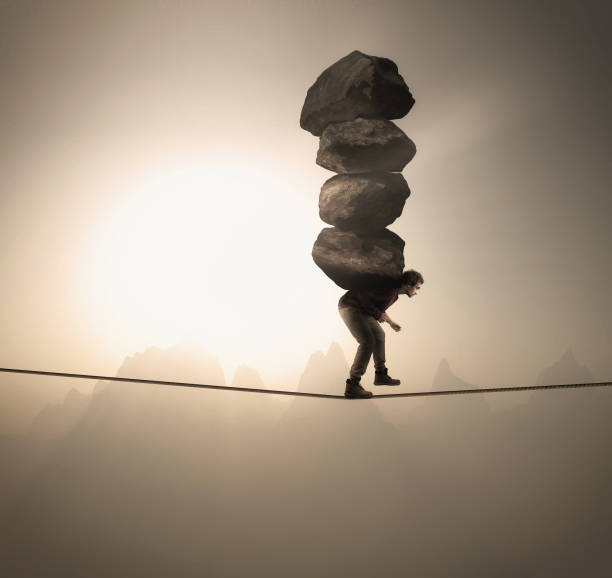Man carries a stack of big rocks while balancing on a rope at high altitude . Man carries a stack of big rocks while balancing on a rope at high altitude . carrying stock pictures, royalty-free photos & images
