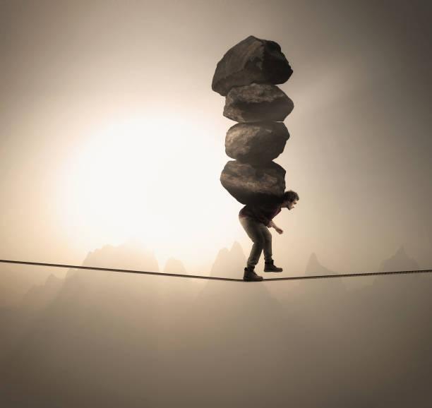 人類在高空用繩子平衡時, 攜帶著一疊大石頭。 - 重的 個照片及圖片檔
