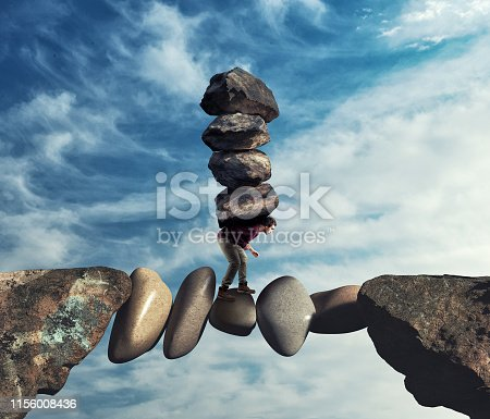 Man carries a stack of stones on a unstable path between two mountain peaks.