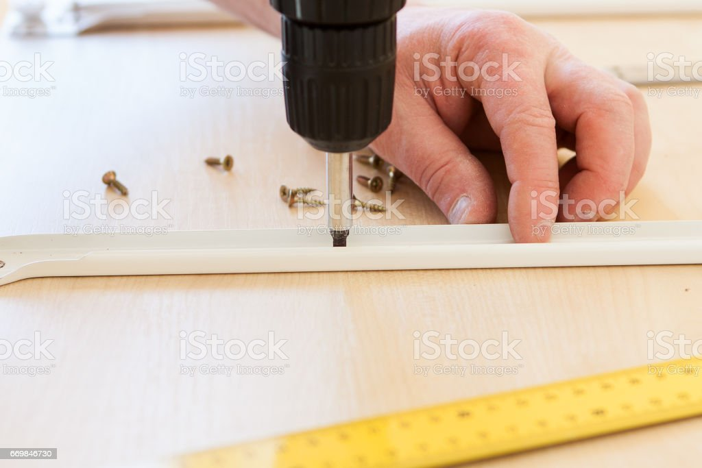 A man carries out the assembly of furniture stock photo