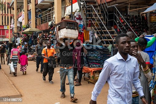 Kampala, Uganda - January 12th, 2020:Unidentified man carries suitcases on his head down a street of Kampala, Uganda. Carrying on head is a common practice both for men and women in Uganda.