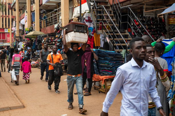 Man carries suitcases on his head down a street of Kampala, Uganda. stock photo
