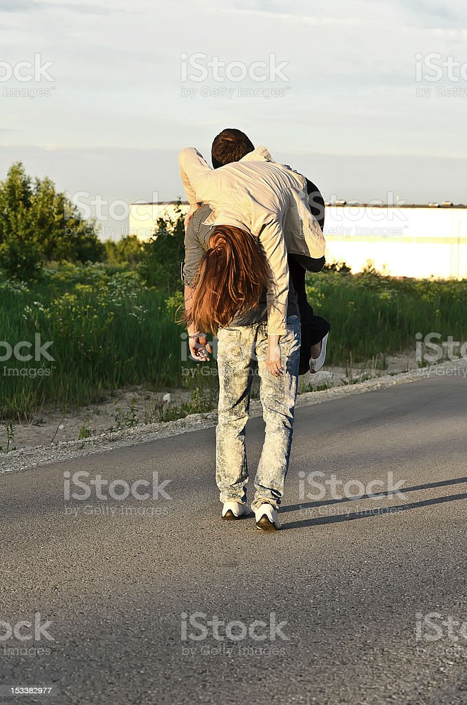 Man carring a young woman on his shoulder. stock photo