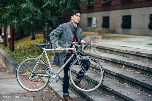 812812808istockphoto Man carrying a bicycle 870271048