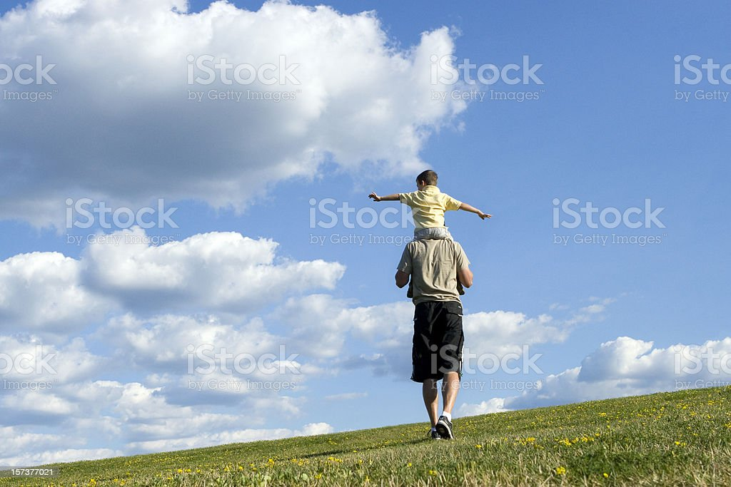 A man carrying a boy on his shoulders in a grass field royalty-free stock photo