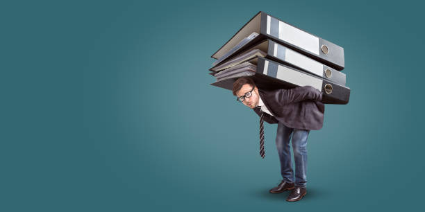 Man carrying a giant stack of folders A businessman with a straining expression is carrying an enormous stack of folders. The size of the folders is comically large. overworked stock pictures, royalty-free photos & images