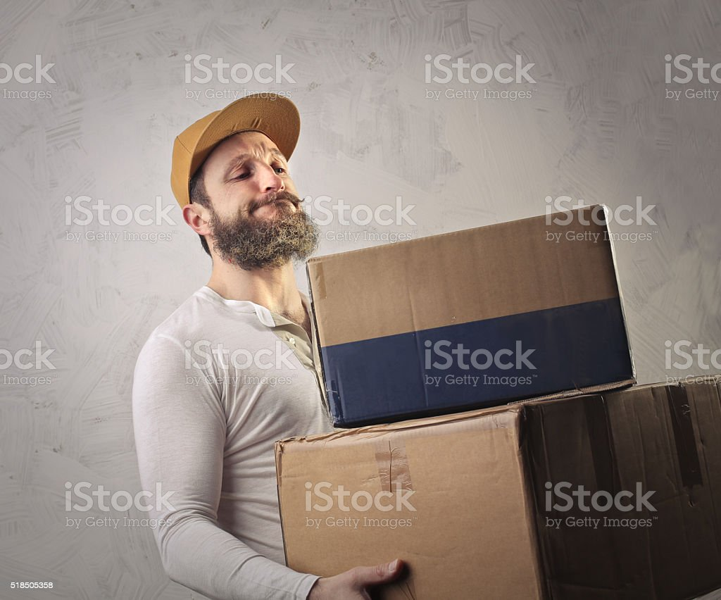 Man carrying a pile of boxes stock photo