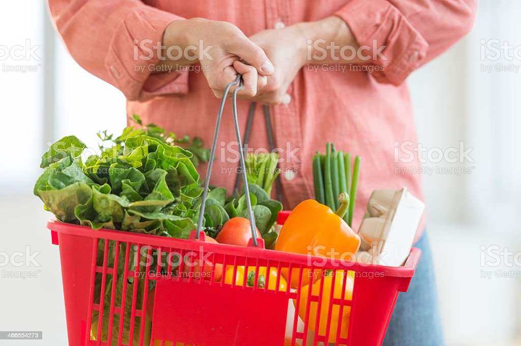 A man carrying a red basket full of vegetables stock photo