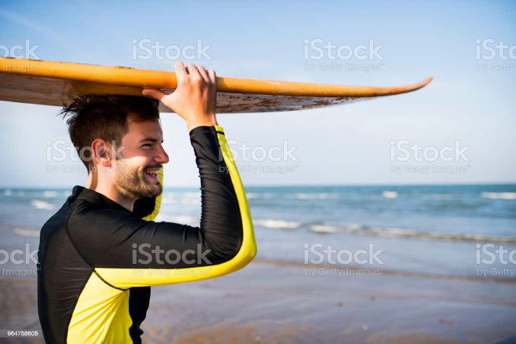 A man carrying a surfboard royalty-free stock photo
