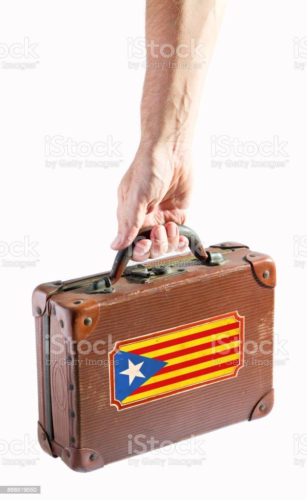 Homem carregando uma mala antiga com bandeira da Catalunha - foto de acervo