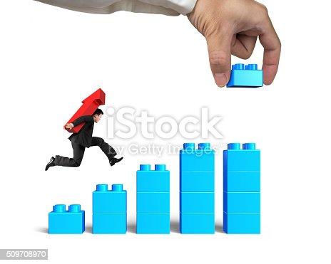 452598975 istock photo Man carrying arrow up running bar graph block hand building 509708970