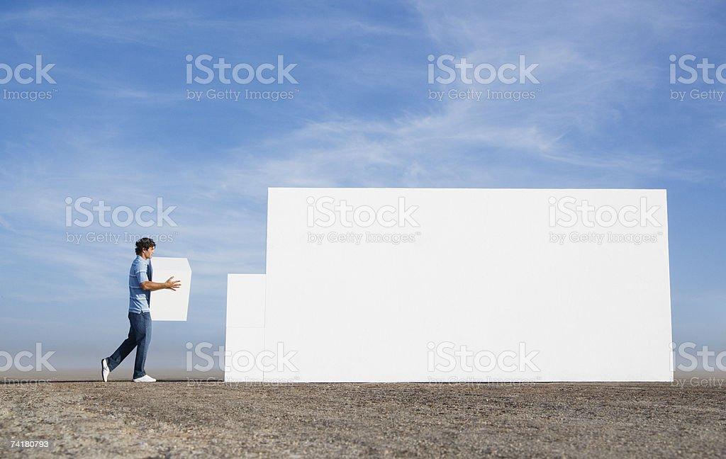 Homem carregar bloco e a parede de construção ao ar livre foto de stock royalty-free