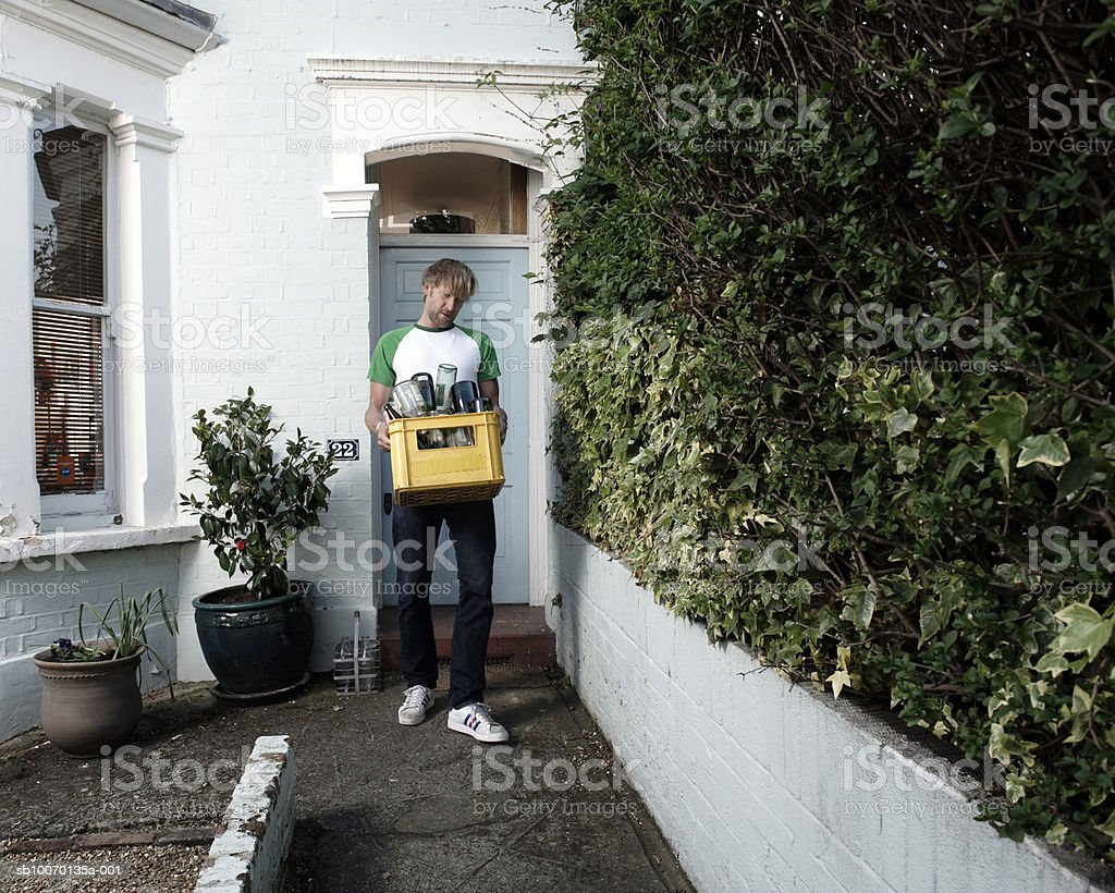 Man carrying bottles for recycling outside house 免版稅 stock photo