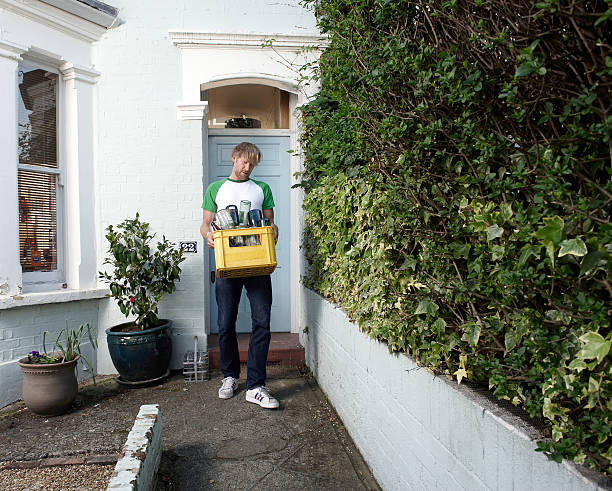 Man carrying bottles for recycling outside house stock photo