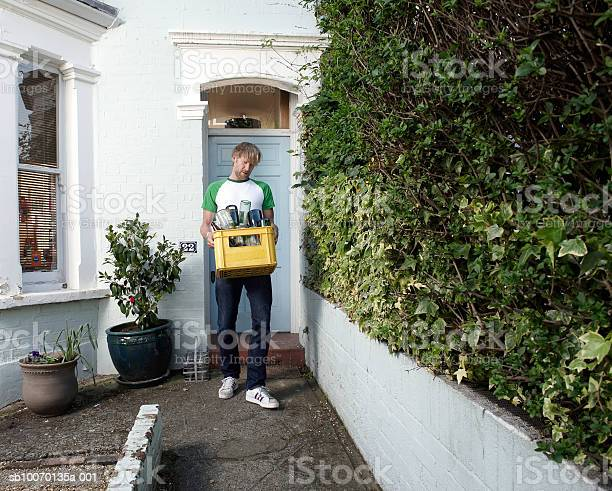 Man Carrying Bottles For Recycling Outside House Stock Photo - Download Image Now