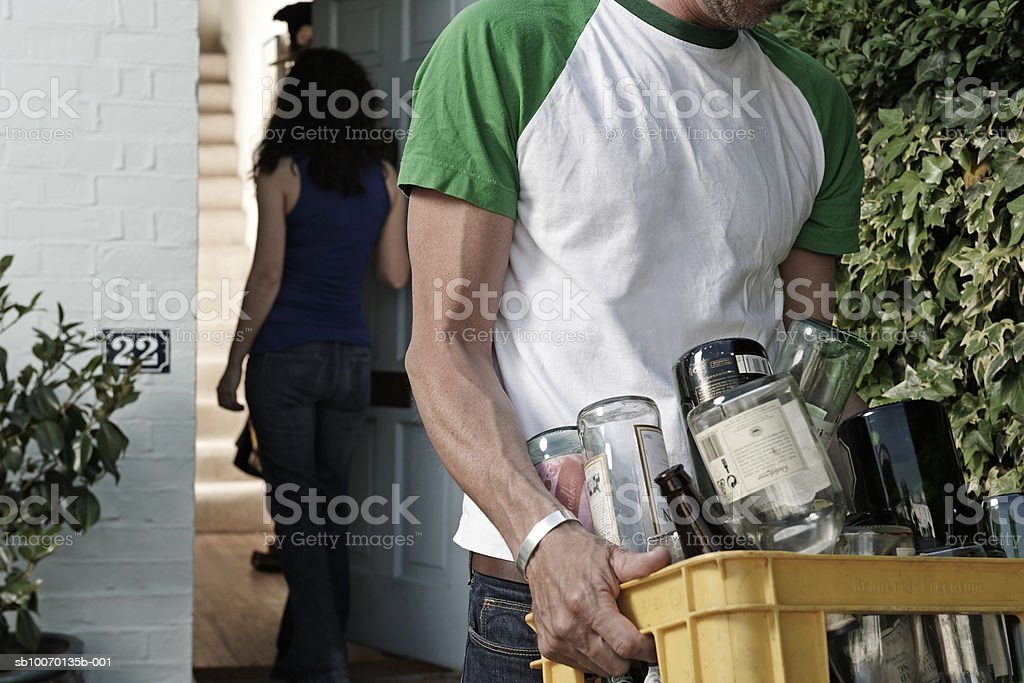 Man carrying bottles for recycling outside house, woman in doorway, mid section 免版稅 stock photo