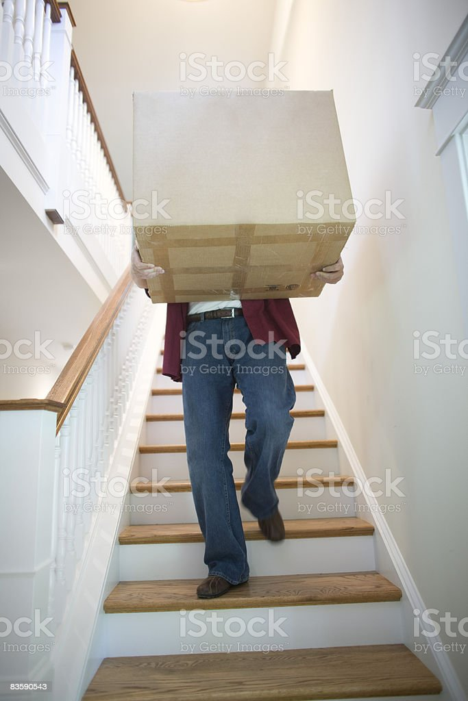 Man carrying box down stairs  40-44 Years Stock Photo