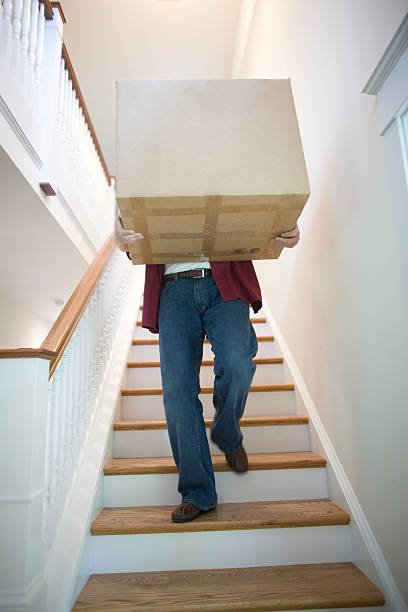 Man carrying box down stairs stock photo
