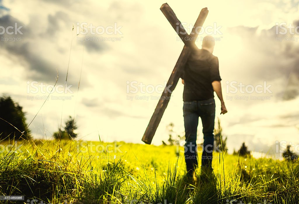 Man Carrying Cross of Christ on His Shoulder stock photo