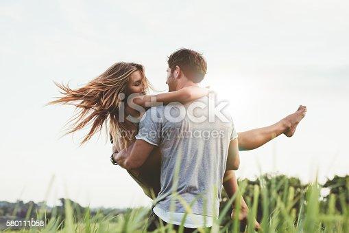 istock Man carrying girlfriend in  grass field 580111058