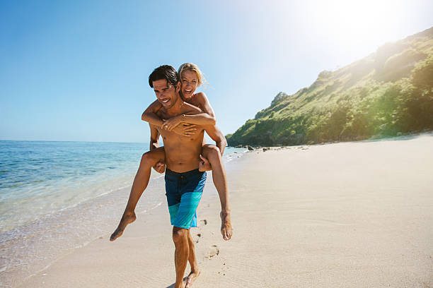 Man carrying girlfriend on his back along the beach stock photo
