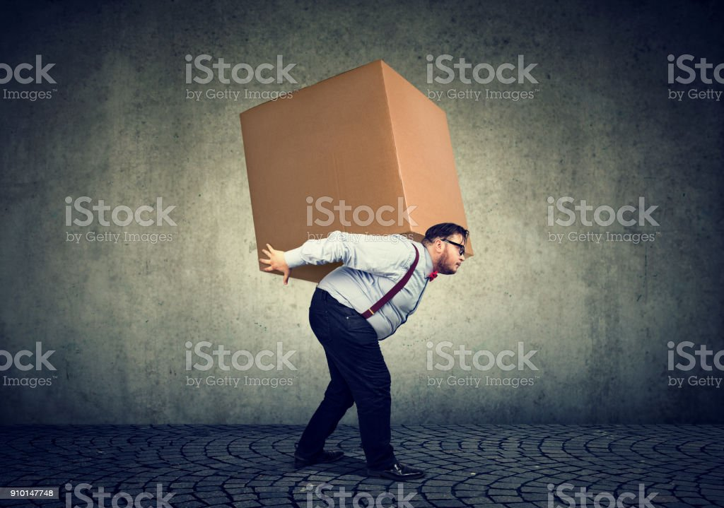 Man carrying heavy box on back stock photo