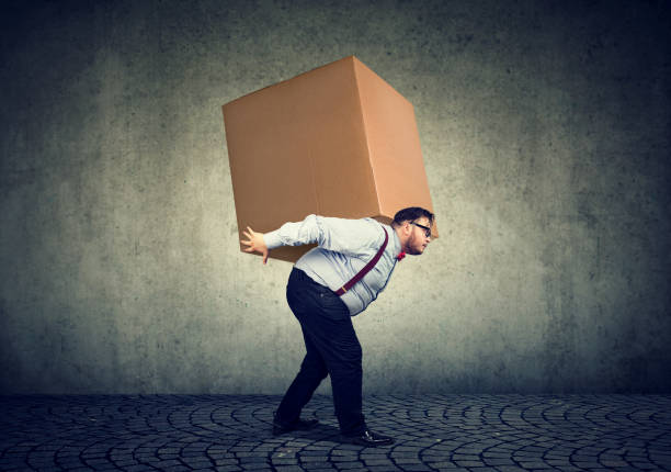 man carrying heavy box on back - carrying stock pictures, royalty-free photos & images