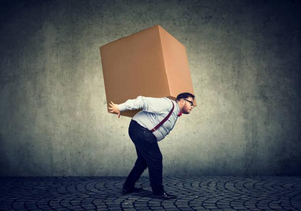 Man carrying heavy box on back stock photo
