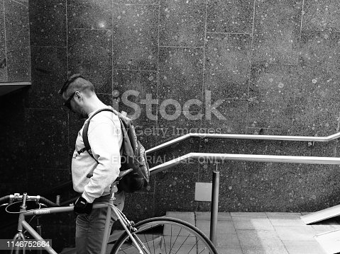 812812808istockphoto A man carrying his bicycle into the underpass 1146752664