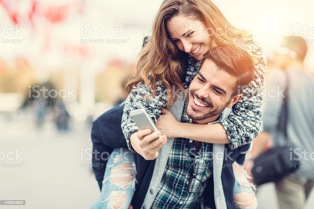 Man carrying his girlfriend on piggyback for selfie stock photo