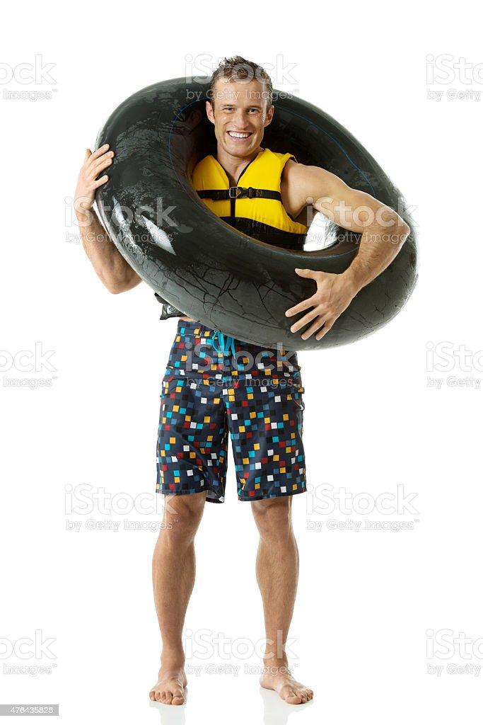 Man carrying inner tube stock photo