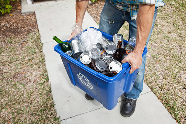 Man carrying recycle bin Low section of man carrying recycling bin. bottle bank stock pictures, royalty-free photos & images
