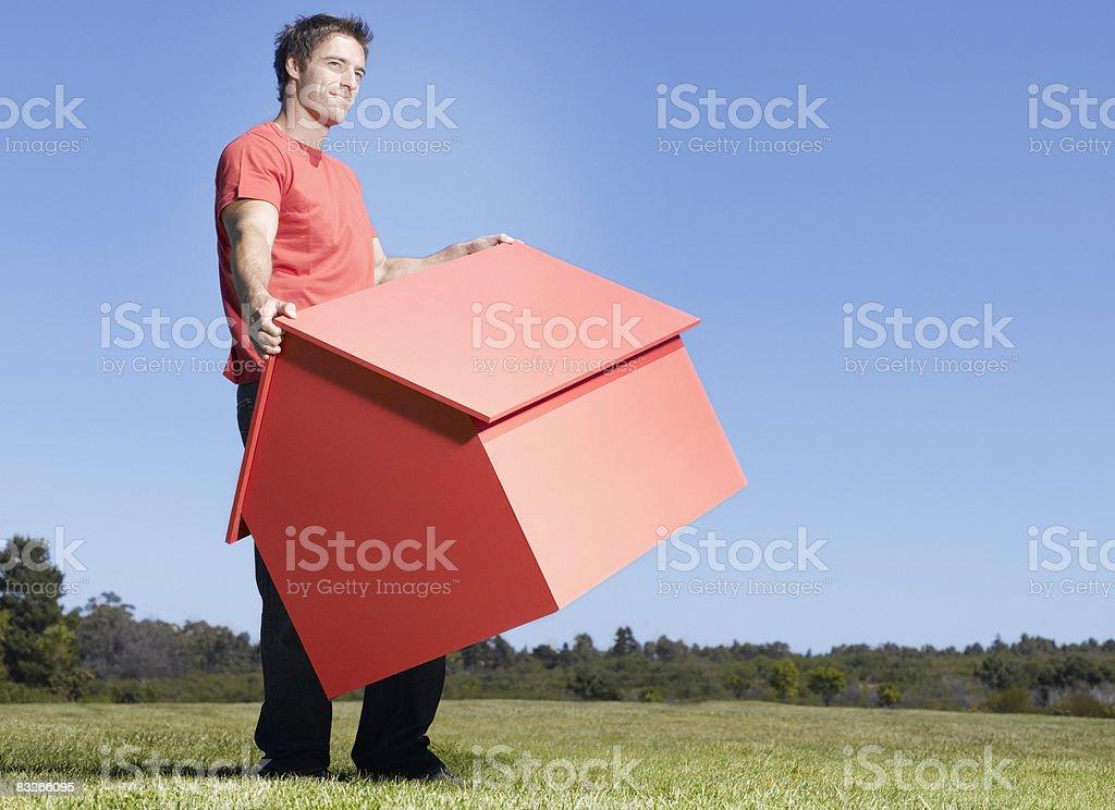 Mann mit kleinen Modell Haus im Feld – Foto