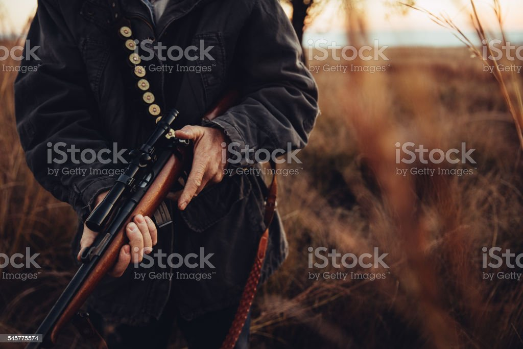 Man carrying sniper and cartridge in wilderness stock photo