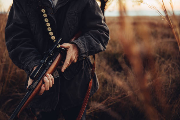 Man carrying sniper and cartridge in wilderness Man carrying sniper and cartridge in wilderness. Long dry grass is surrounding him. hunter stock pictures, royalty-free photos & images
