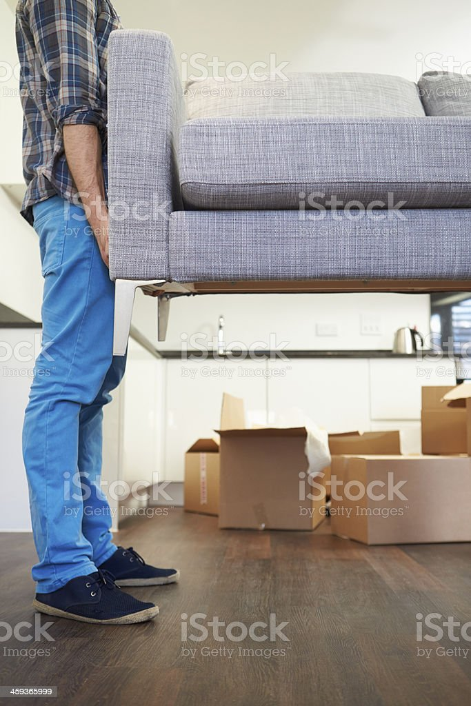 Man Carrying Sofa As He Moves Into New Home stock photo