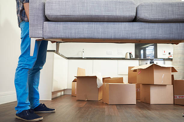 man carrying sofa as he moves into new home - physical activity stock photos and pictures